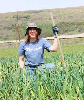 Grey Duck Garlic, Susan smiling in garlic field